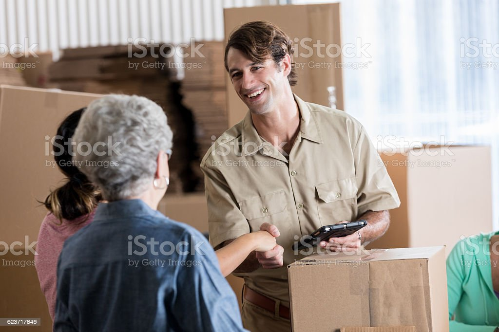 Friendly delivery man greets female small business owners stock photo