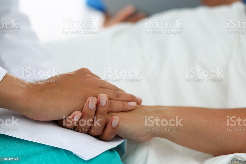 Friendly female doctor hands holding patient hand stock photo