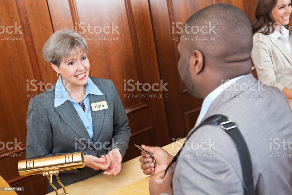 Friendly front desk lady helping hotel guest royalty-free stock photo