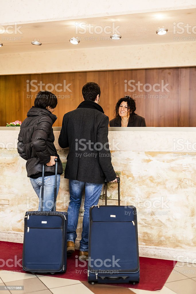 Friendly front desk worker helping guest check into hotel stock photo