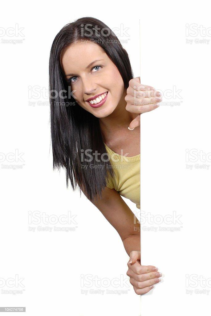 Friendly girl peeking round a white board royalty-free stock photo