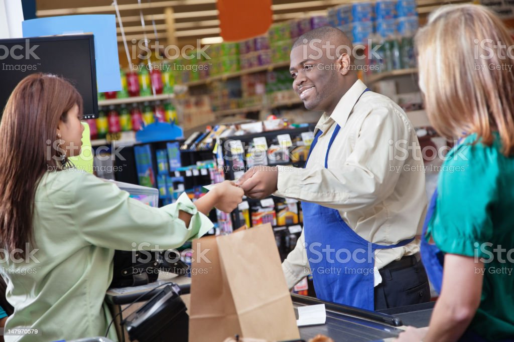 Friendly grocery store clerk giving change to customer royalty-free stock photo