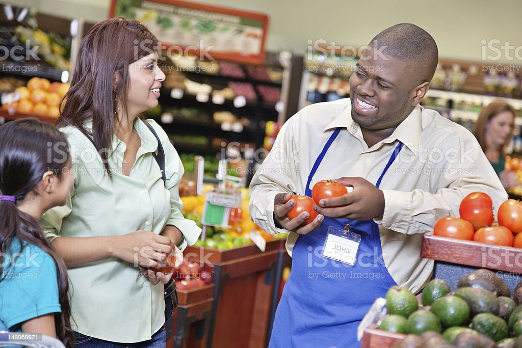 Friendly grocery store worker helping customers in supermarket royalty-free stock photo