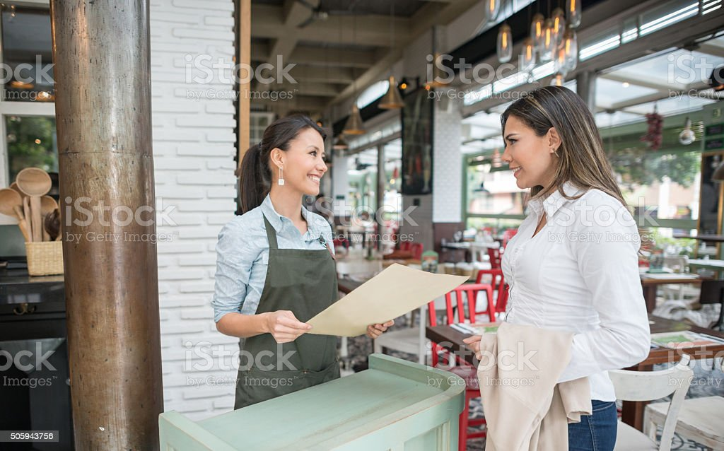 Friendly hostess working at a restaurant stock photo