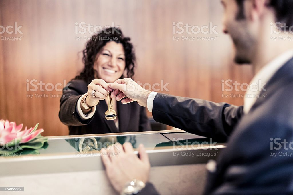 Friendly hotel worker helping guest check-in royalty-free stock photo
