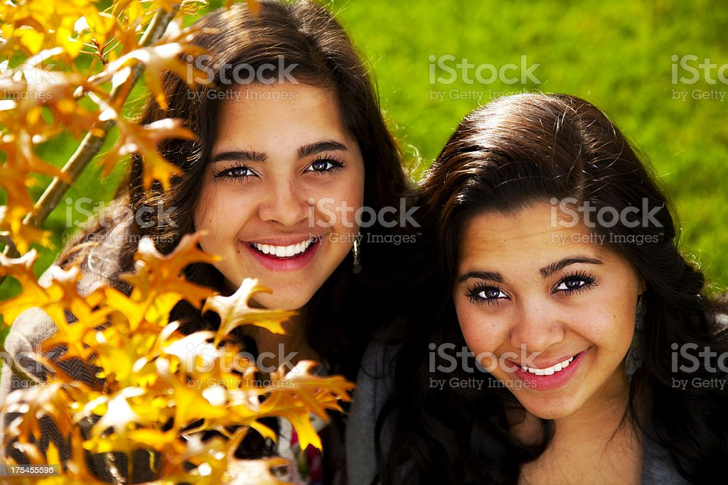 Friendly Latina Twins in Colorful, Natural Setting stock photo