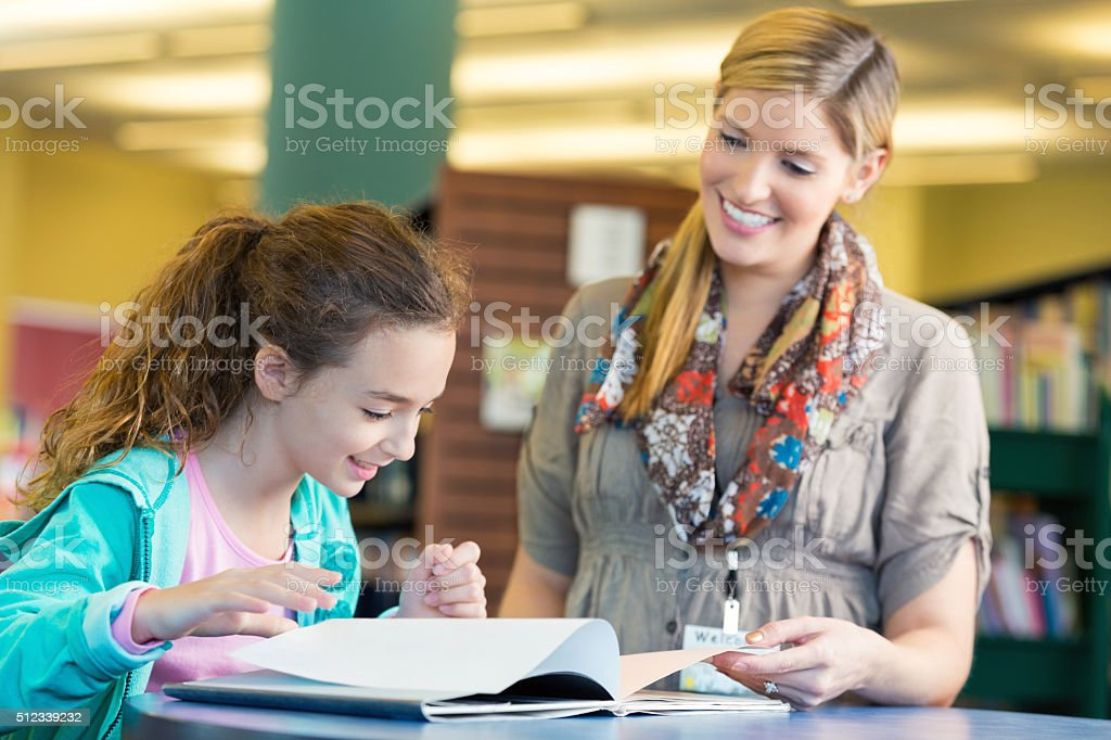 Friendly librarian helping elmentary age girl read book in library stock photo