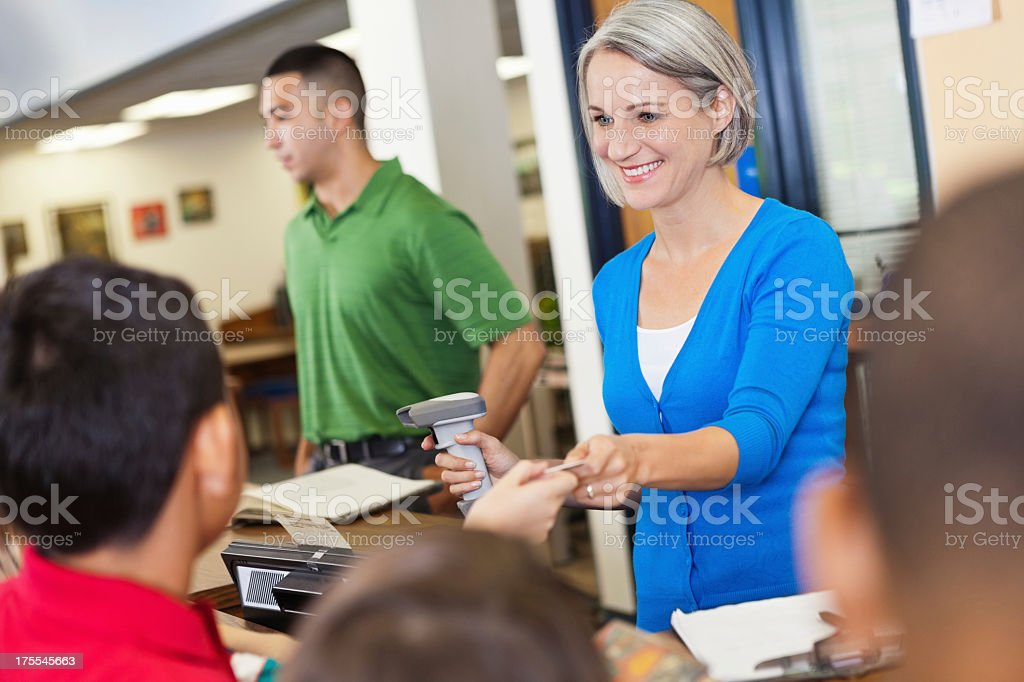 Friendly Librarian Helping Student Check Out Library Books royalty-free stock photo