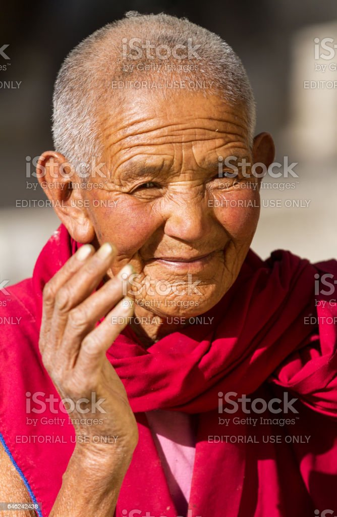 Friendly looking and smiling old buddhist nun from Jelichun nunnery stock photo