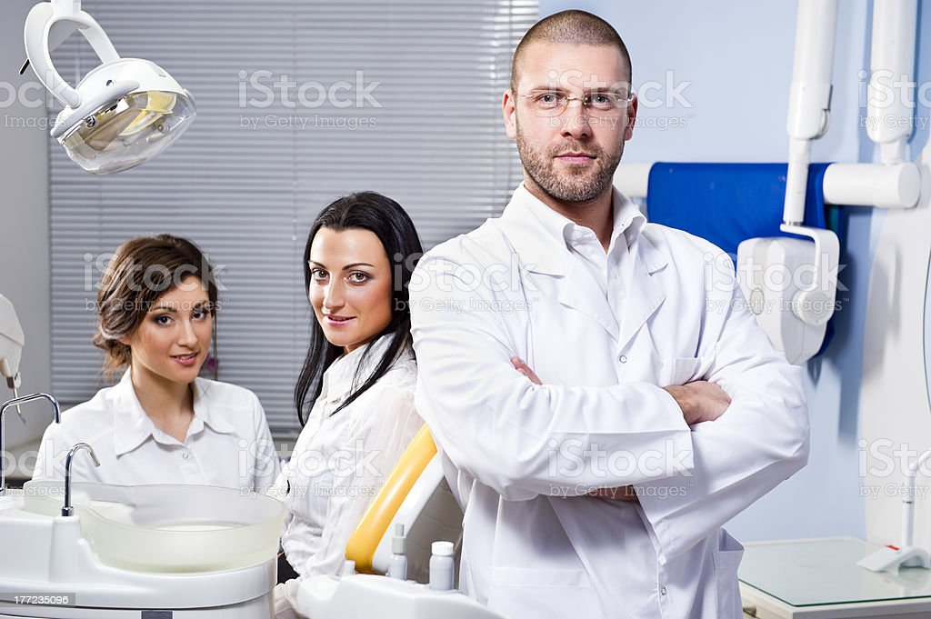 Friendly male dentist, assistant and smiling patient royalty-free stock photo