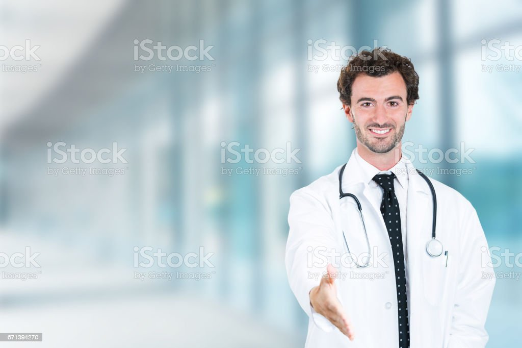 friendly male doctor extending arm giving handshake smiling stock photo