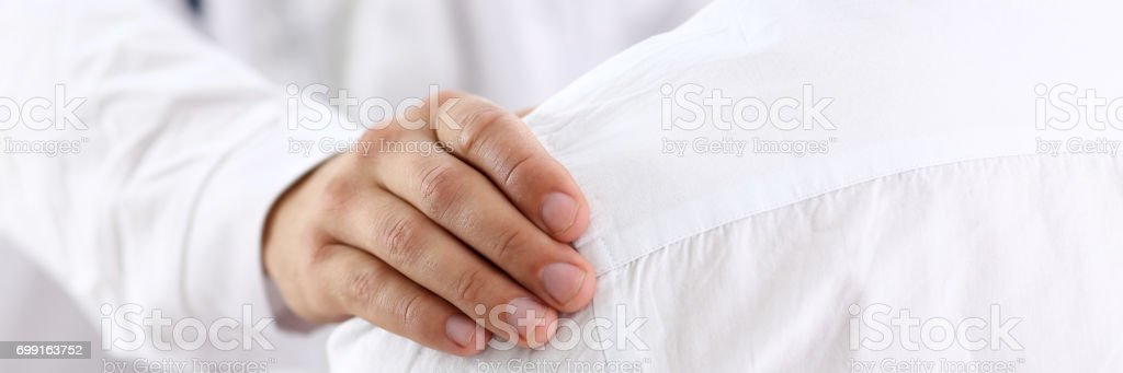 Friendly male doctor hold patient shoulder in office during reception stock photo