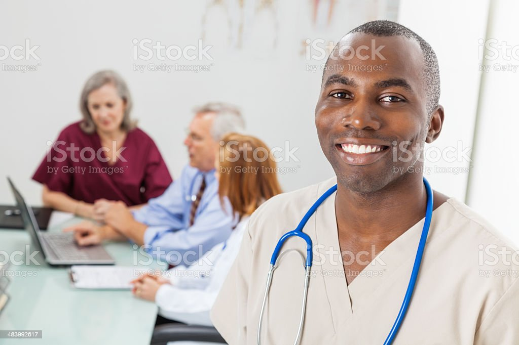 Friendly male nurse in hospital or doctors office meeting stock photo
