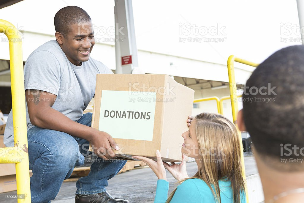 Friendly male volunteer accepting box of donations at food bank stock photo
