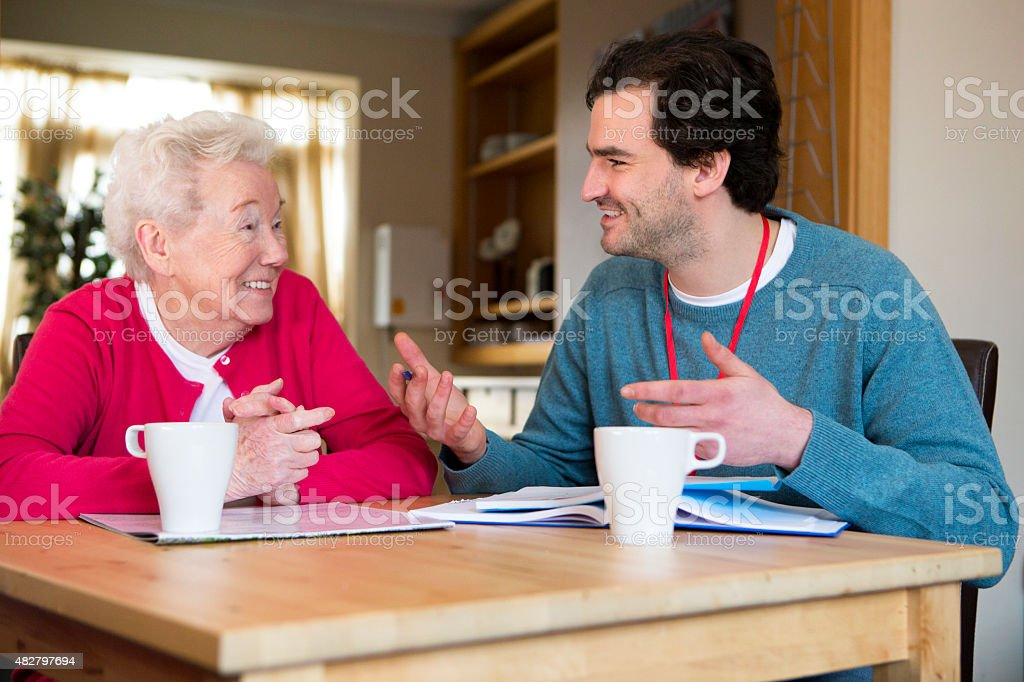 Friendly male volunteer assisting a senior woman with paperwork. stock photo