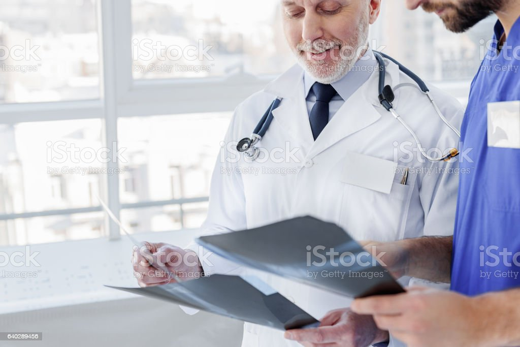Friendly mature general practitioner working with assistant stock photo