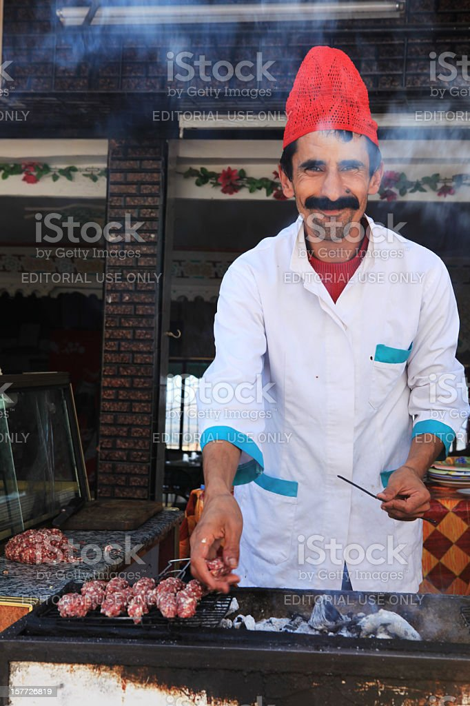 Friendly Moroccan man doing the barbeque ready for kebab royalty-free stock photo