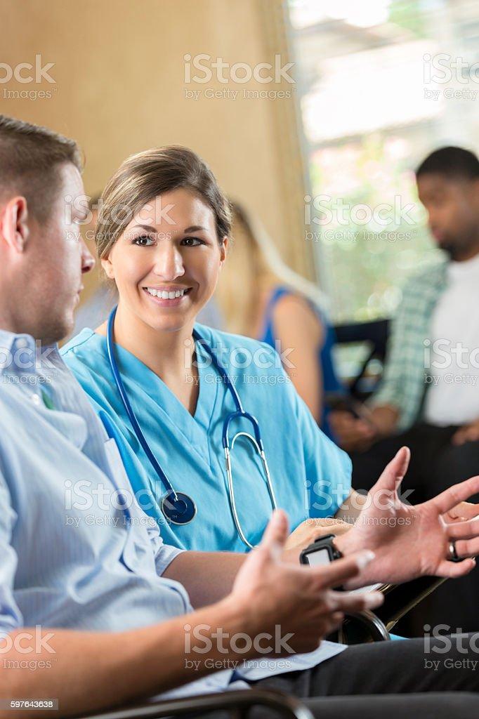 Friendly nurse examining patient in hospital triage center, stock photo