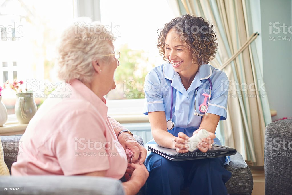 friendly nurse home visit stock photo