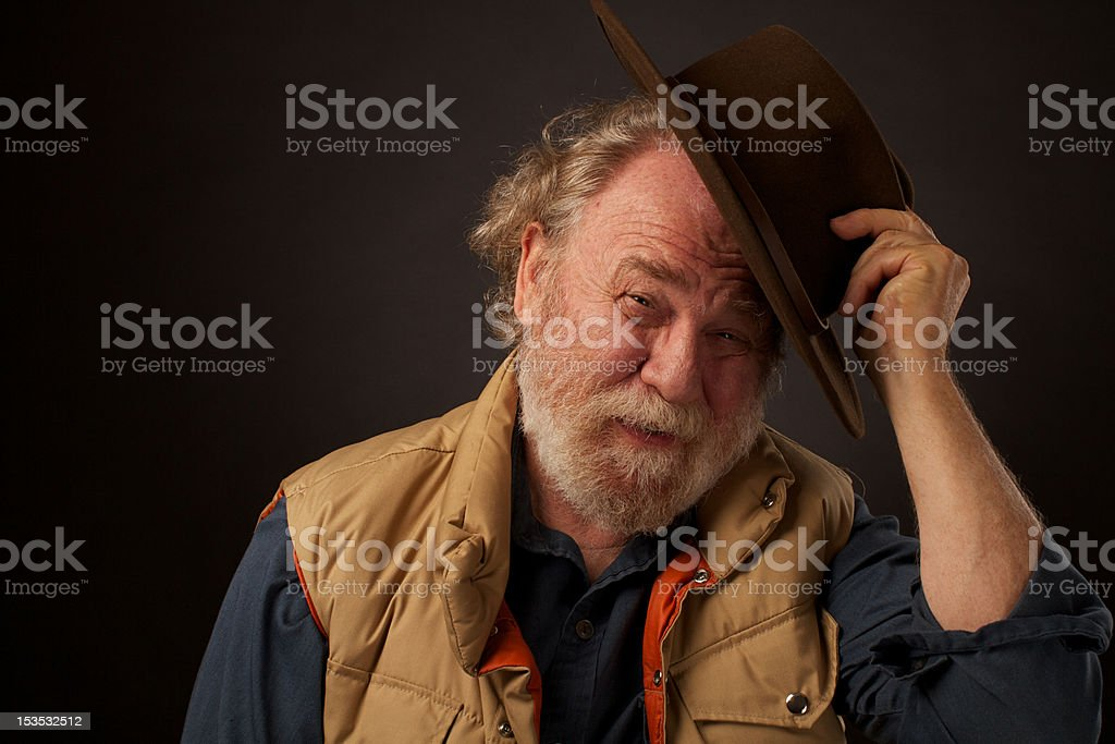 Friendly old bearded outdoors man tipping his felt hat stock photo