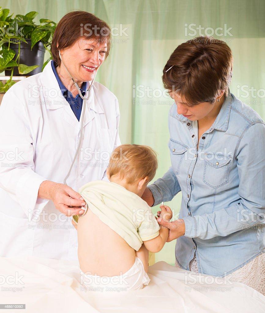 friendly pediatrician doctor examining baby stock photo