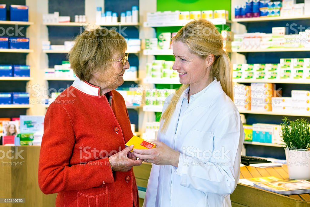 Friendly pharmacist giving customer prescription. stock photo