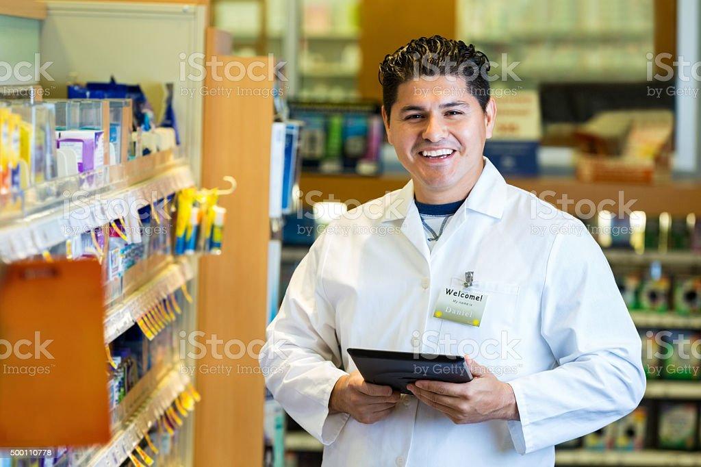 Friendly pharmacist in local pharmacy using digital tablet stock photo
