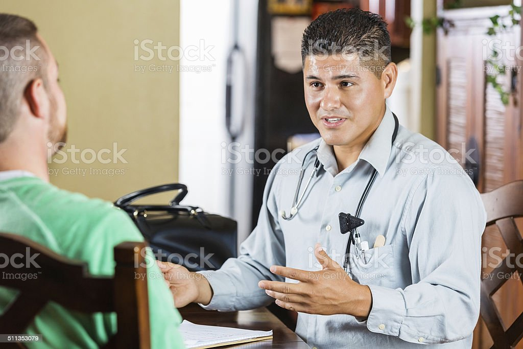 Friendly physician talking with patient during house call appointment stock photo