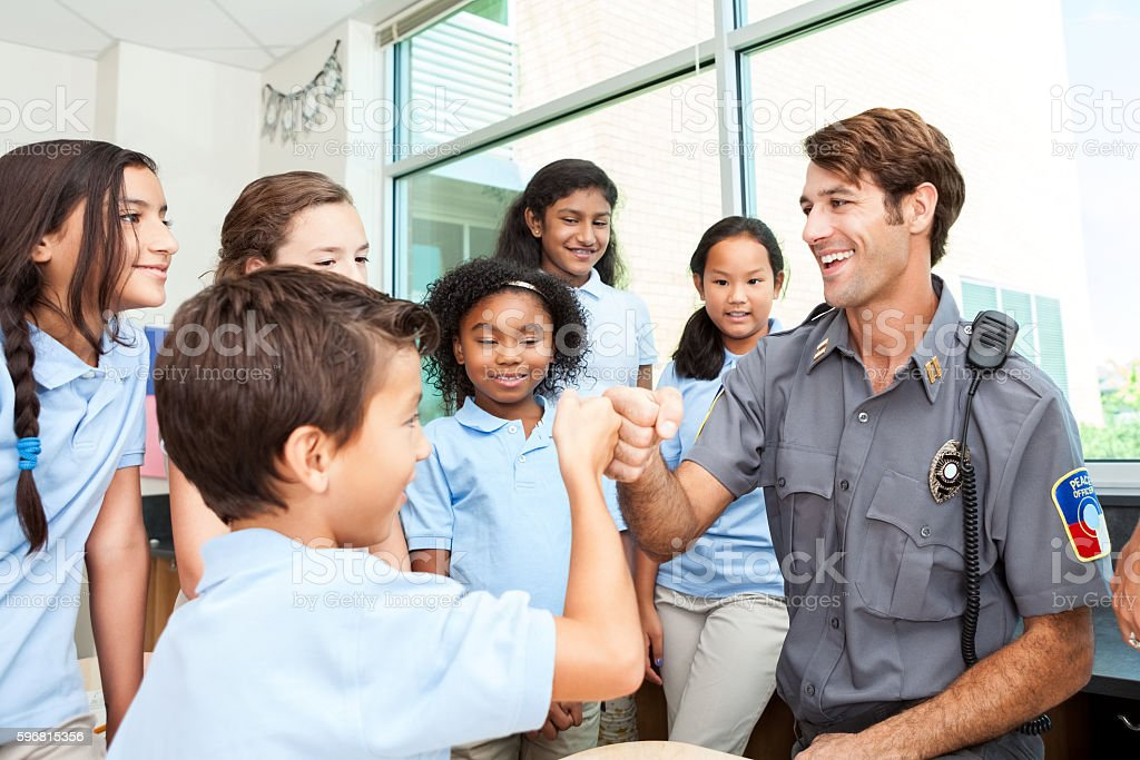 Friendly police officer gives fist bump to student stock photo