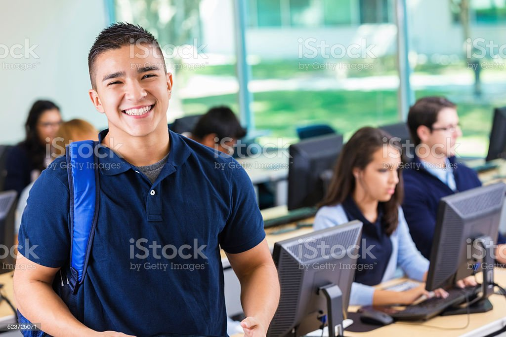 Friendly private high school student smiling in modern computer lab stock photo