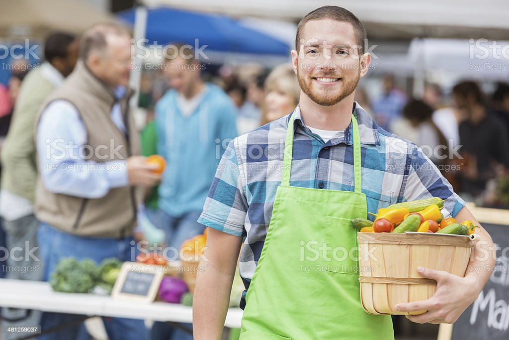 Friendly produce vendor smiling at outdoor farmers market booth stock photo