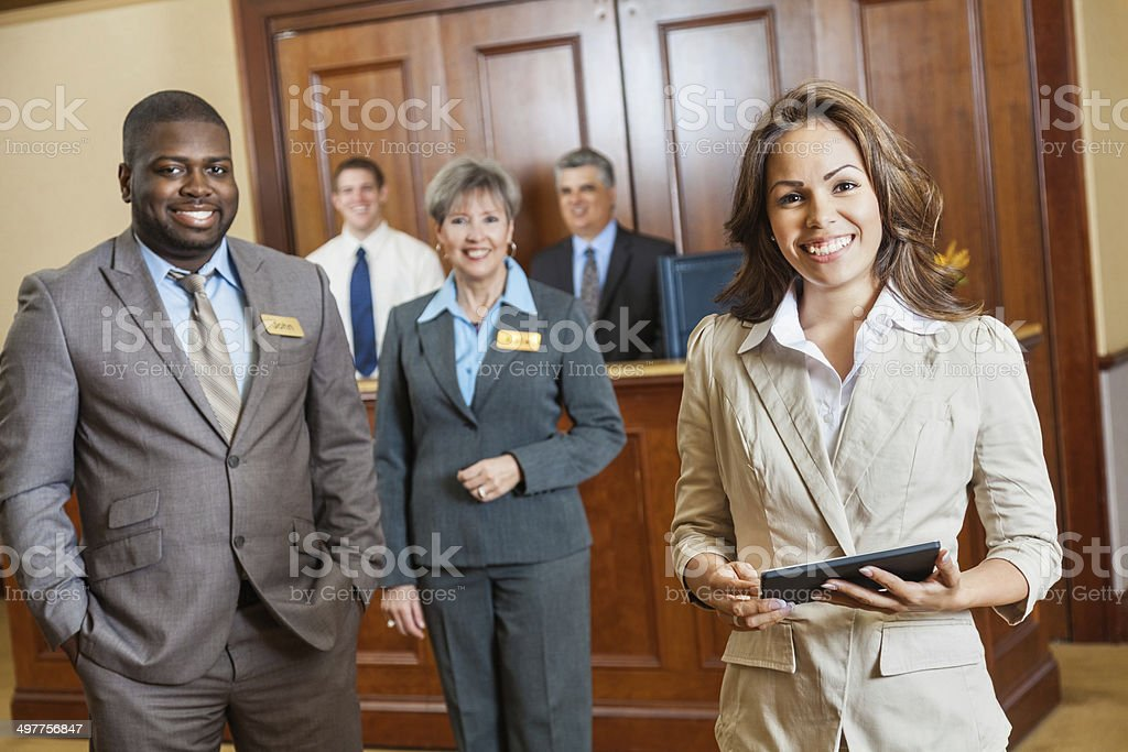 Friendly professional hotel staff with managers, clerks, and administrators stock photo