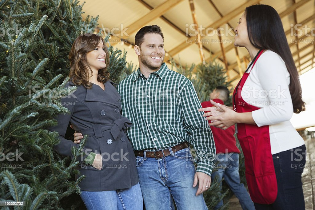 Friendly salesperson helping family choose Christmas tree to purchase royalty-free stock photo
