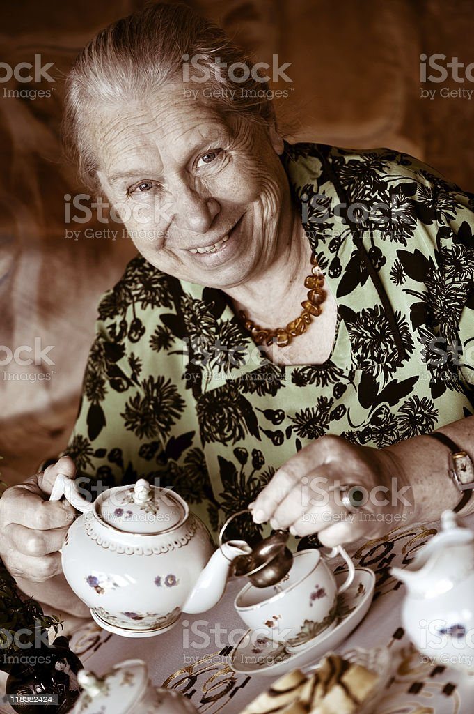 Friendly senior woman drinking a cup of tea royalty-free stock photo