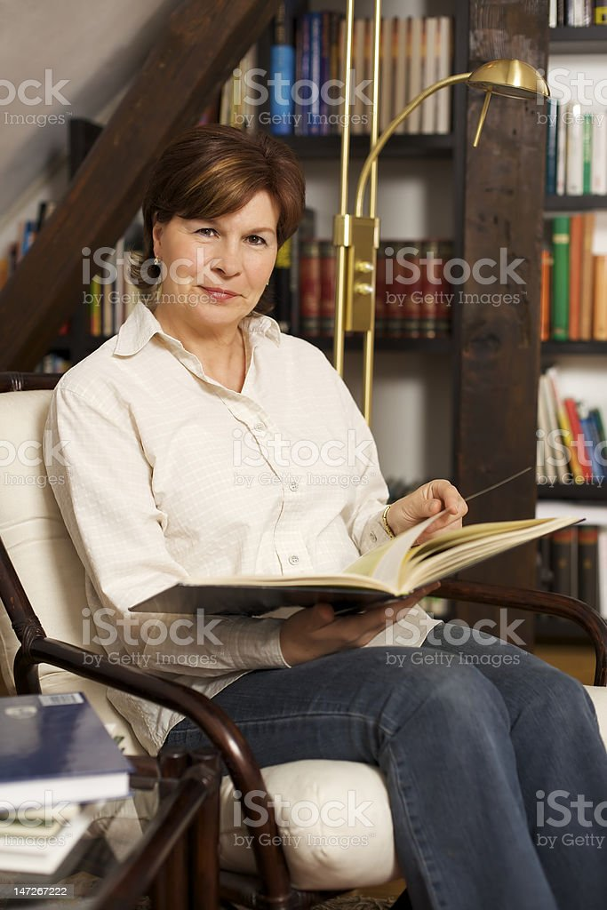 Friendly senior woman sitting and reading a book royalty-free stock photo