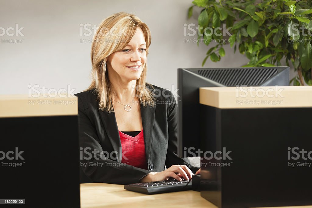 A friendly smiling woman bank teller working behind the bank counter...