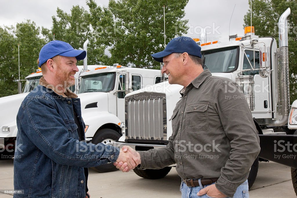 Friendly Trucker Handshake and Cooperation in Front of  Semi Truck stock photo