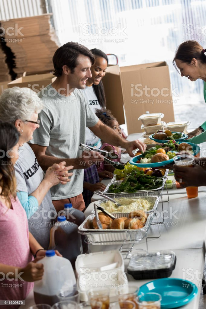 Friendly volunteers serve people in soup kitchen stock photo