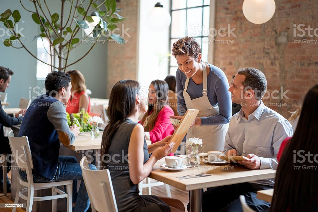 Friendly waitress serving couple at a restaurant stock photo