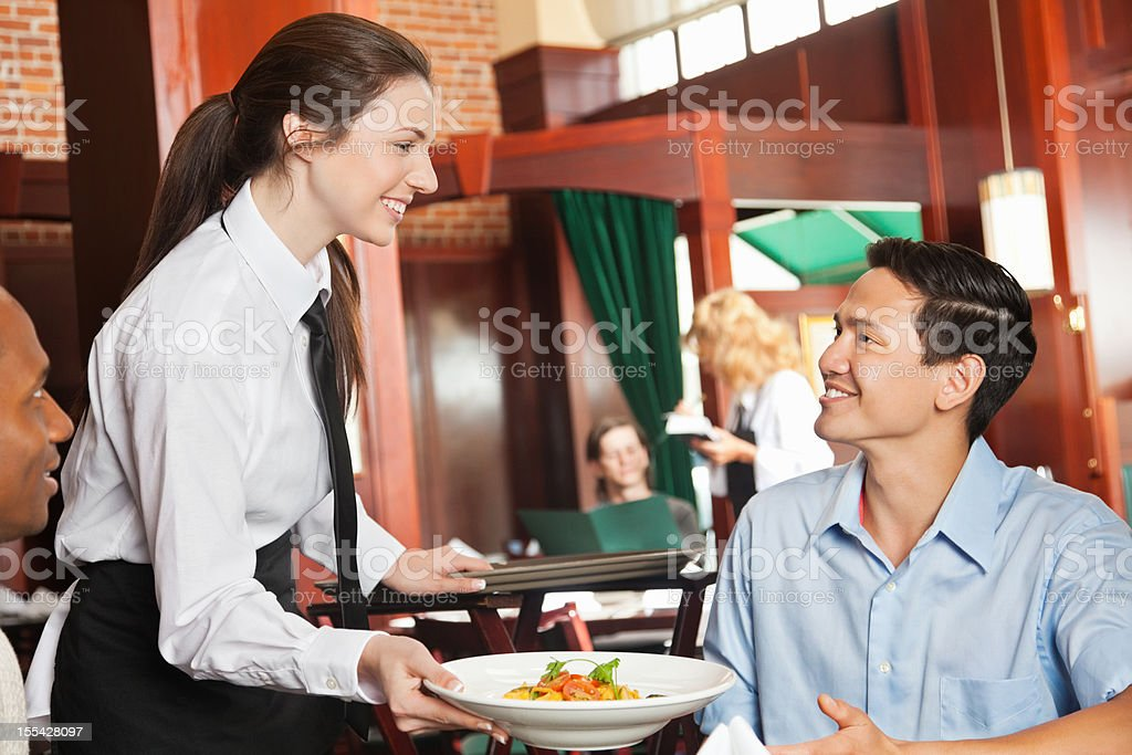 Friendly waitress serving food to guests at nice restaurant stock photo
