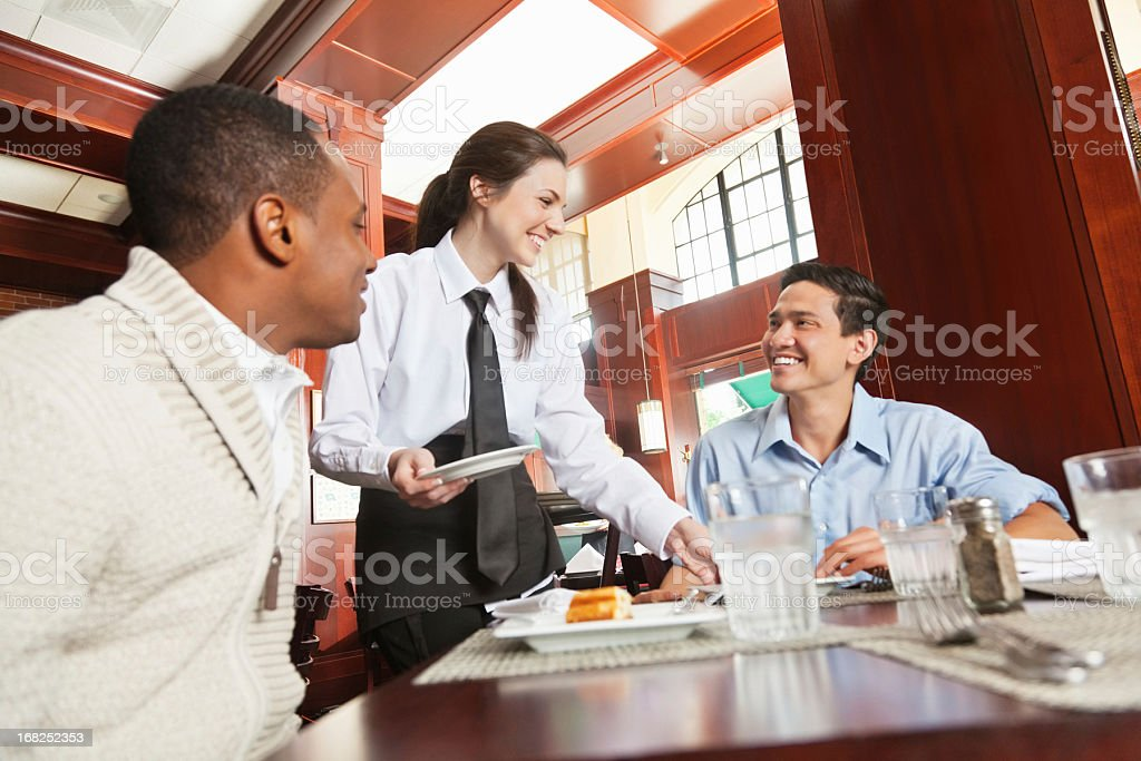 Friendly waitress serving guests in nice restaurant stock photo