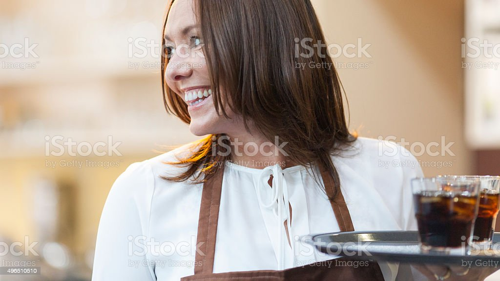 Friendly waitress working in a cafe stock photo