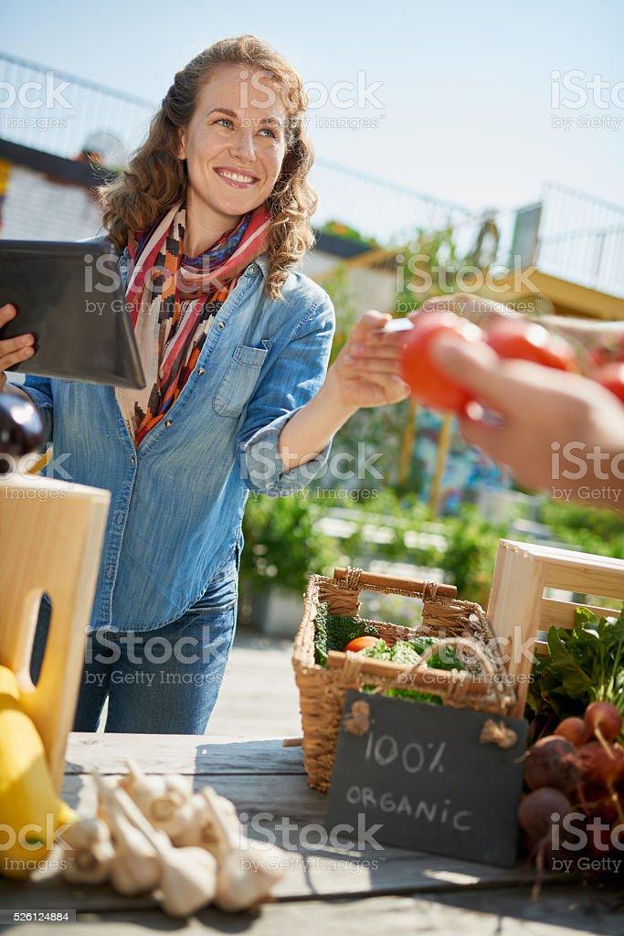 Friendly woman tending an organic vegetable stall at a farmer stock photo