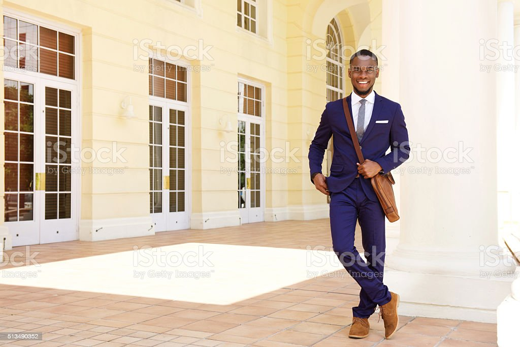 Friendly young businessman standing by building stock photo