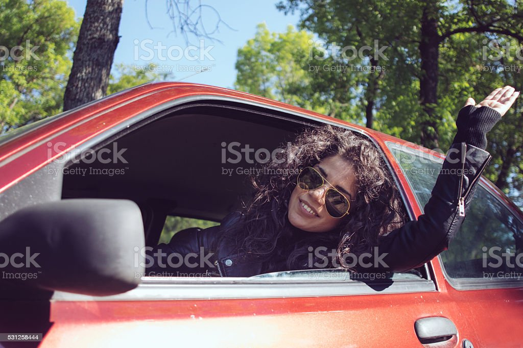 Friendly young girl driving her red car and waving. stock photo