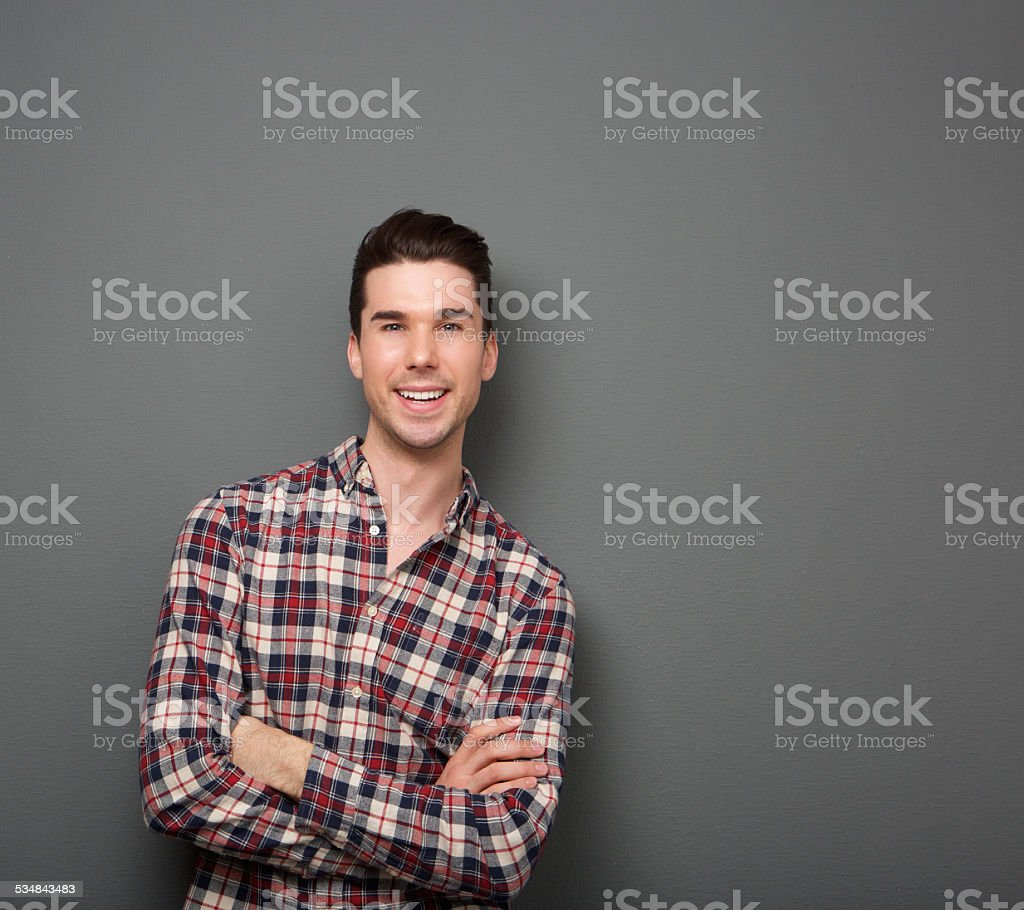 Friendly young man smiling with arms crossed stock photo