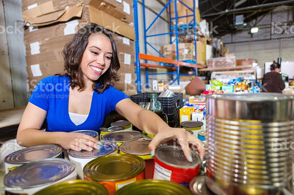 Friendly young woman sorting canned food donations for charity drive stock photo