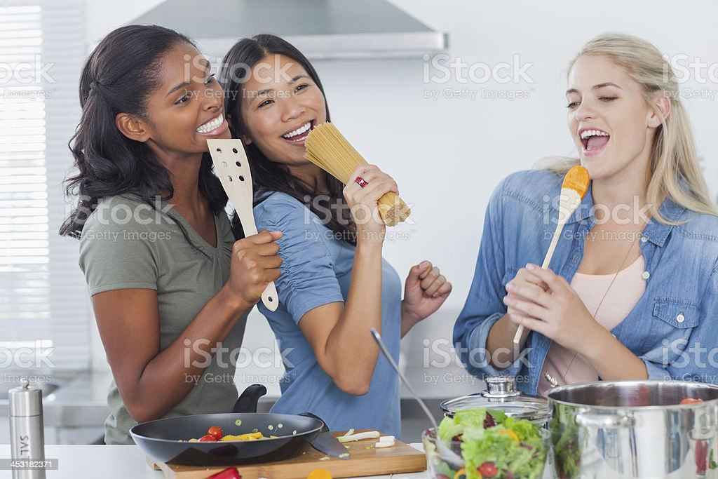 Friends acting silly while making dinner stock photo