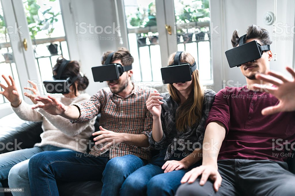 friends addicted to the VR simulator togetherness stock photo