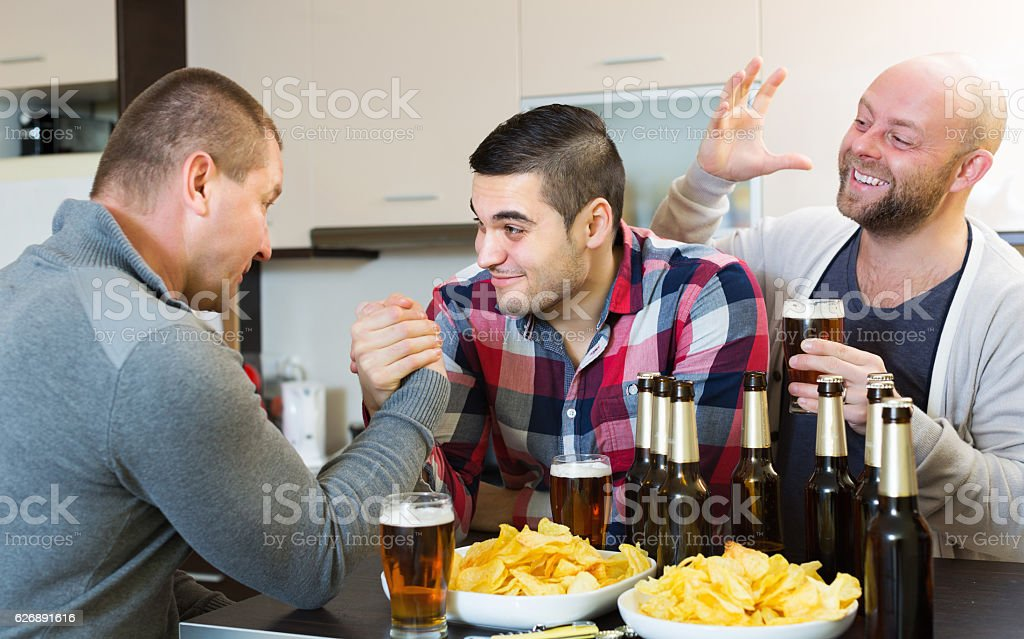 Friends armwrestling at the table stock photo